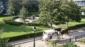 A horsedrawn carriage on a narrow road beside a grassy courtyard