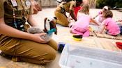Un empleado de Disney sostiene un pelícano de felpa mientras otro miembro del elenco interactúa con 3 niños