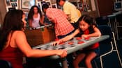 Mom and daughter play checkers on an oversized board
