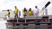Debout sur un bateau ponton, des visiteurs mettent leur canne à l'eau tout près du Disney's Contemporary Resort