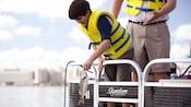 Un jeune visiteur avec un gilet de sauvetage sort un achigan à grande bouche fraîchement pêché alors que son père le regarde