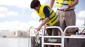 A young Guest in a life vest pulls a fresh-caught largemouth bass from the water as his dad watches