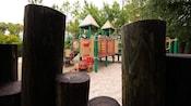 Uma vista rodeada por toras de madeira de um playground infantil