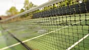 Close-up of a tennis net and its court in the background