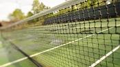 Primer plano de una red de tenis con su cancha en el fondo