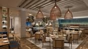Several tables and chairs in the dining area of Amare restaurant, as well as an open kitchen
