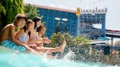 A family making a splash in the pool at the Disneyland Hotel.