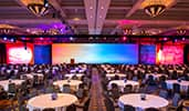 A large convention room with dining tables, colorful lights and monitors