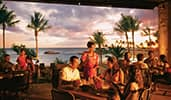 Attendees enjoying outdoor evening dining by the water at Disneys Aulani Resort in Hawaii
