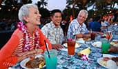 Attendees enjoying food and drinks at a Hawaiian luau