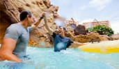2 Guests high five each other after completing an inner tube ride at Aulani Resort