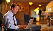 A man works on his laptop in the lobby of a Disney Resort hotel