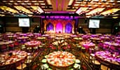 A colorful ballroom with round tables and chairs, flowers, a stage and 2 monitors