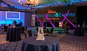 A ballroom with round tables, chairs, a small stage and 2 large screens that say Disney Meetings and Events, Use Our Imagination