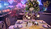 A ballroom with dining tables decorated with candles and elegant floral displays