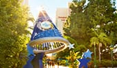 A view of the Disneyland Hotel and signage for the hotel on a Sorcerer Mickey Hat sculpture