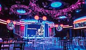 A modern event space with monitors, colorful lighting and cocktail and standard tables