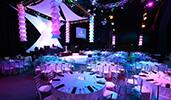 An event space with round dining tables, colorful lights, a monitor and a stage
