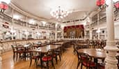 A restaurant with Western flair, polished brass banisters and old fashioned chandeliers