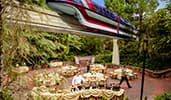 Dining tables set up outside and the Disney Monorail going by