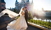 A bride and groom standing in front of Cinderella Castle