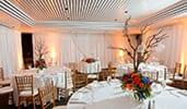 An elegant room with dining tables with twig and floral displays