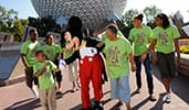 A family wearing matching reunion T shirts meeting Mickey Mouse in Epcot by Spaceship Earth