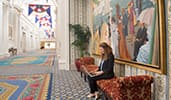 A women works on her laptop in a stunning hall with colorful carpet, flags and paintings at Disneys Yacht Club Resort