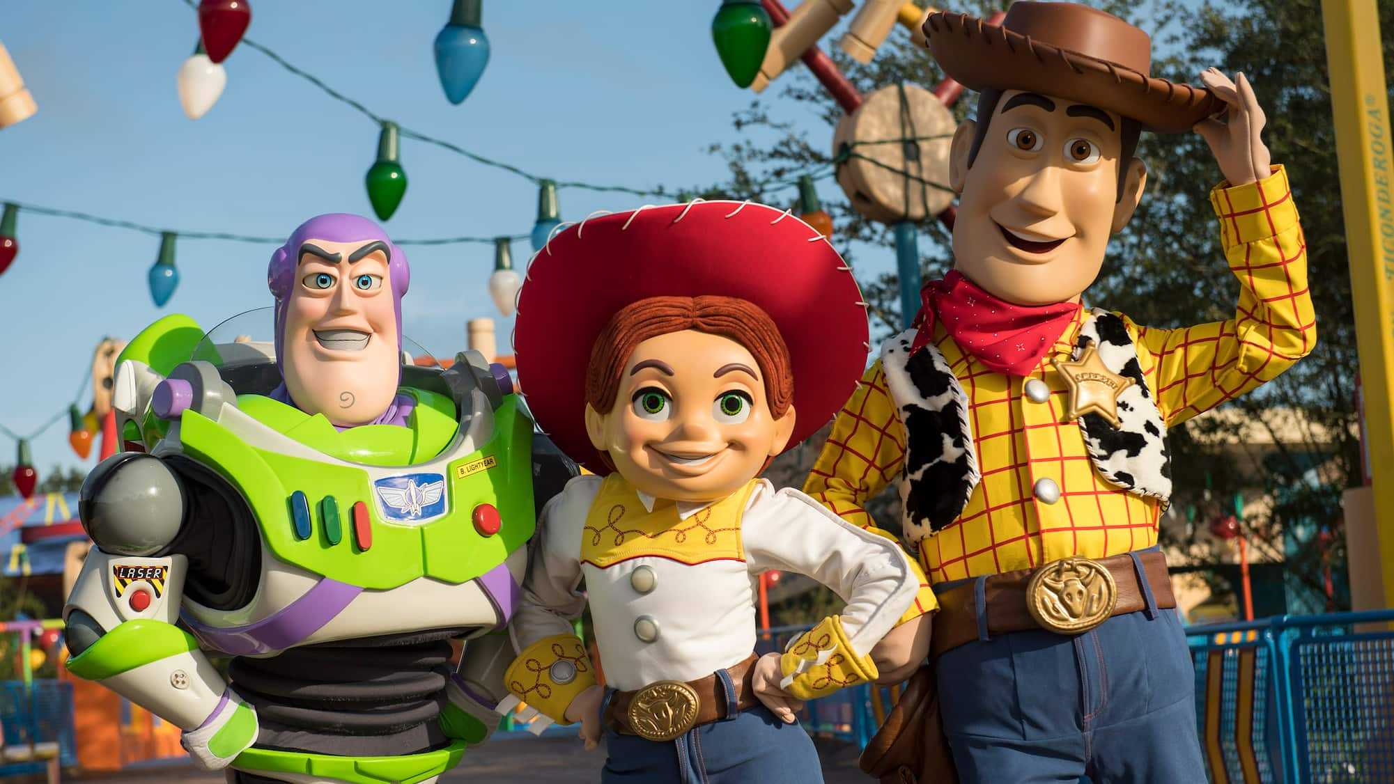 Buzz Lightyear, Jessie and Woody stand together on the streets of Toy Story Land