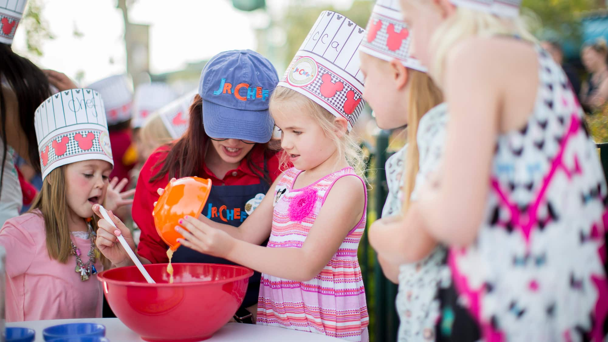 Girls wearing chef hats mix batter in a bowl with the help of a woman wearing a Junior Chef baseball cap