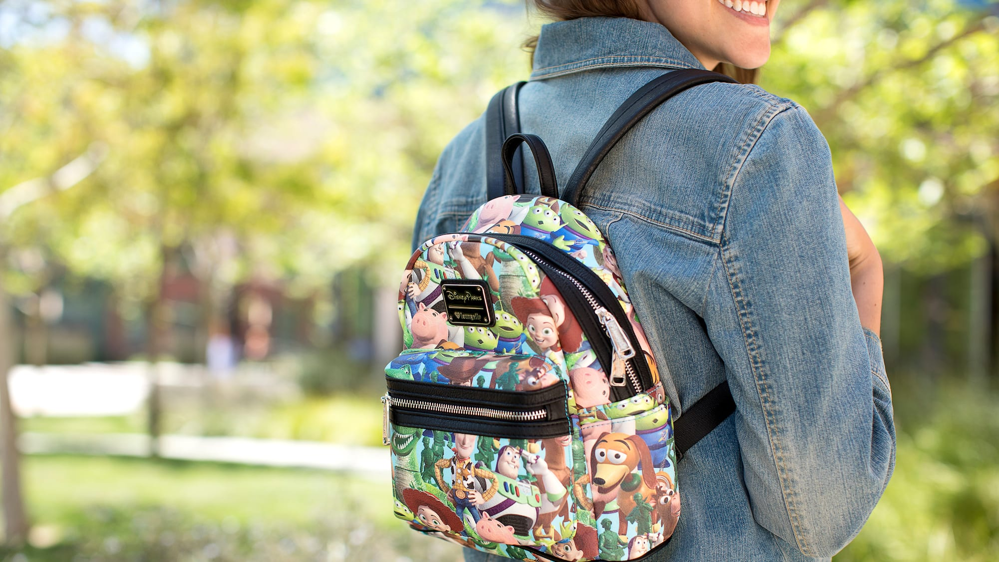 5fcc0bfb2a2 A woman wearing a small backpack with a Toy story themed graphic print