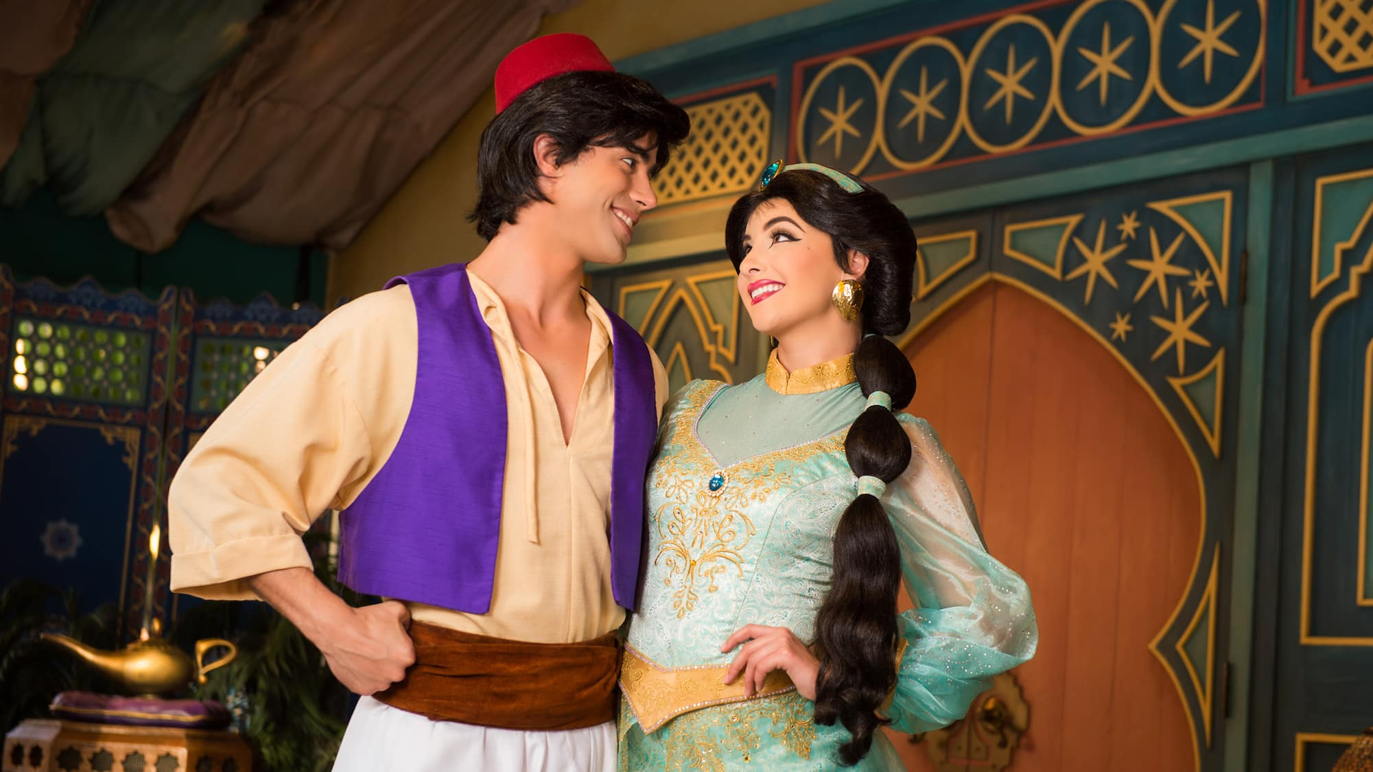 Aladdin and Disney Princess Jasmine stand arm in arm, smile and gaze into each others