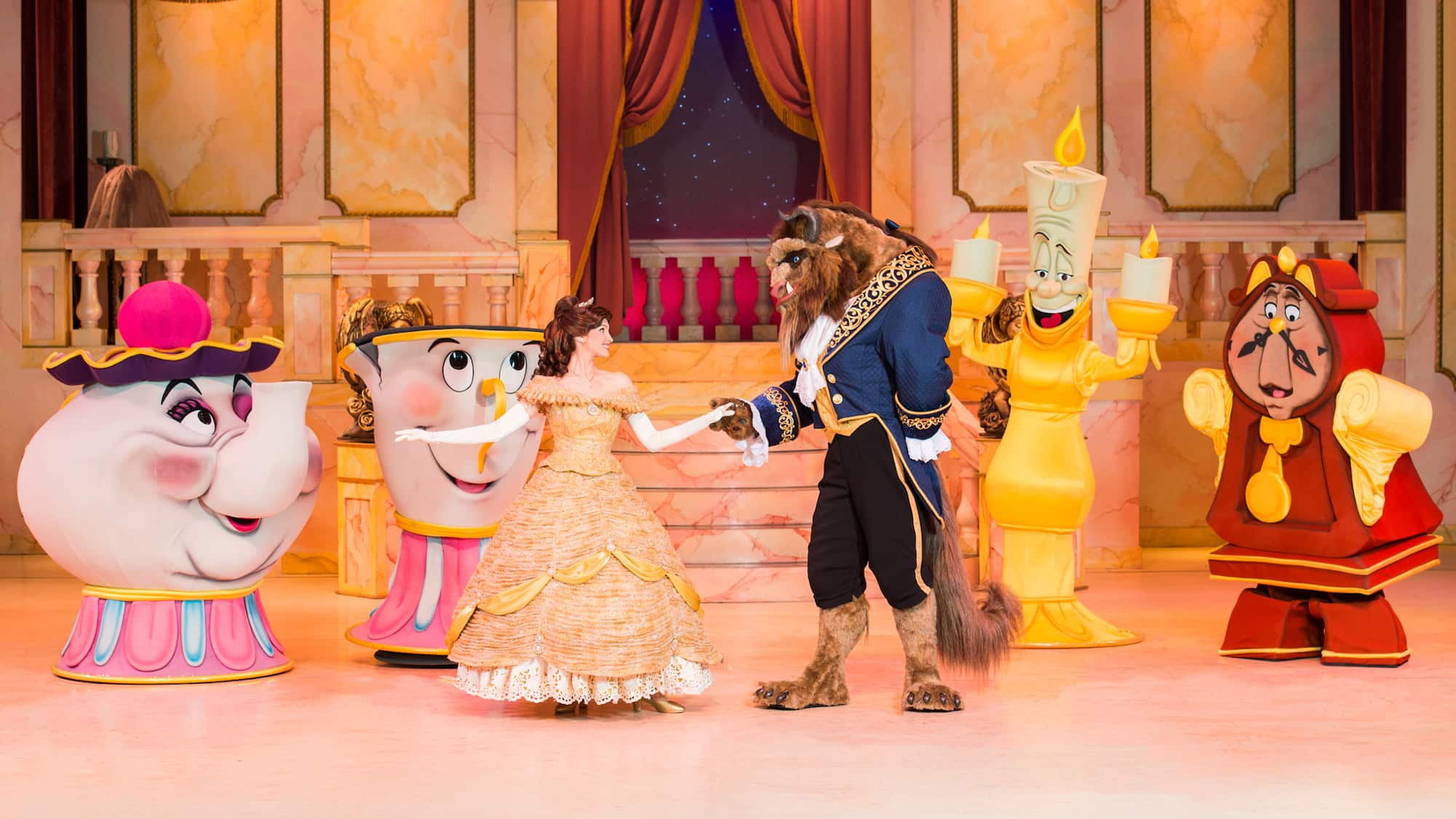 The Beast dances with Belle on stage while Lumiere, Cogsworth, Mrs. Potts and Chip look on in glee