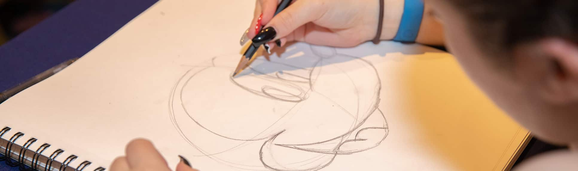 A teenage girl draws a picture of Mickey Mouse on a pad of paper