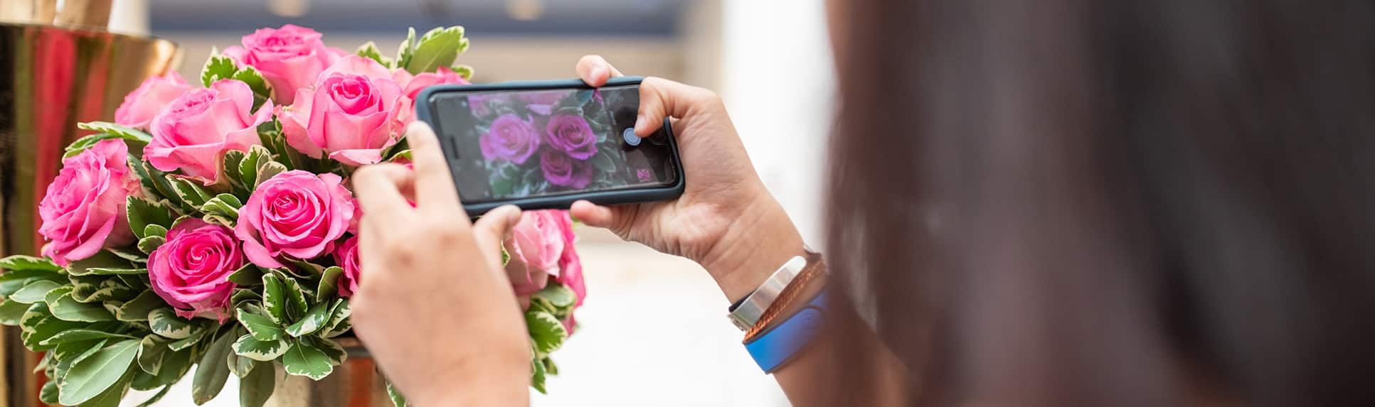 A teenage girl takes a photo of a vase of roses with her mobile phone