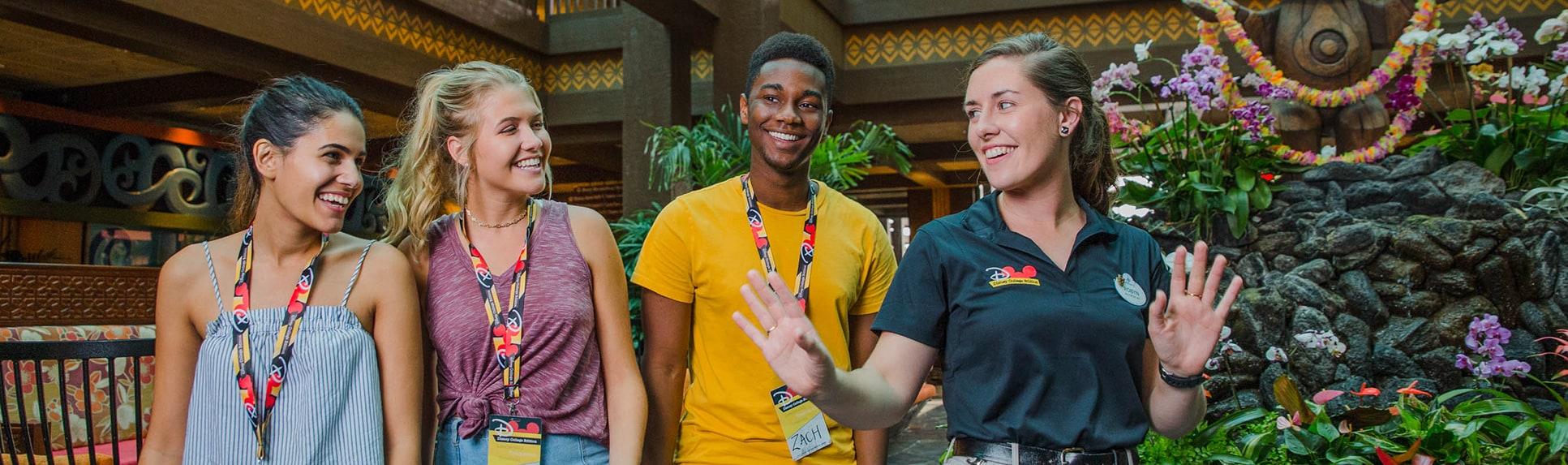 A female Disney Cast Member leads 3 teenage students through a Polynesian themed lobby