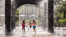Kids in swimsuits splash and play in the sun under a porticoed outdoor fountain and play area