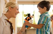 A woman gives a little boy a plush Goofy