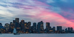 A boat on the Charles River in front of the Boston skyline at dusk