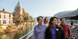 An Adventure Guide and 3 Adventurers pass a stone building and tower as they sail down the Rhône River