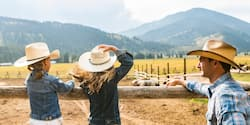 Two girls wearing cowboy hats stand on a wood fence looking at horses in a pen as their father, also wearing a cowboy hat, looks on against a backdrop of mountains