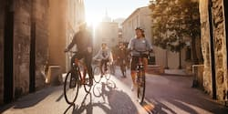 An Adventure Guide and several helmet-clad Adventurers ride bicycles on a street lined with stone buildings in Lyon, France