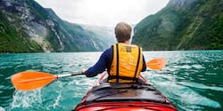 The back of a man paddling a kayak on a river with mountains ahead of him