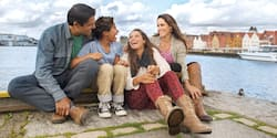 A laughing family sits together on the edge of a river, with old buildings lining the shore