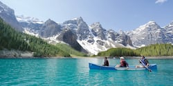 Three people in a canoe paddle across calm water with a backdrop of snow-capped mountains