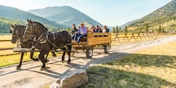 A horse and wagon, filled with people, travel down a dirt road along a wooden fence in valley between nearby mountains