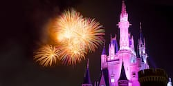 A nighttime firework display in the sky above Cinderella Castle at Tokyo Disneyland in Japan