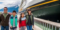 A family of 4 walk on a walkway next to a docked Disney Cruise Line cruise ship with mountains in the background