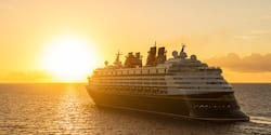 A Disney Cruise Line cruise ship sails on the sea towards the setting sun