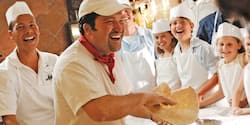 A family in aprons and chef hats watches a chef throw pizza dough